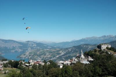 vue de loin, survol de Saint Vincent les forts par deux parapente