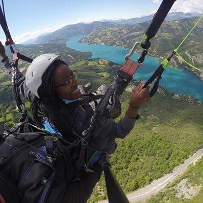 Jeune femme essayant de piloter le parapente biplace.