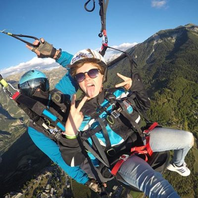 Jeune personne en vol parapente biplace manifestant sa joie.
