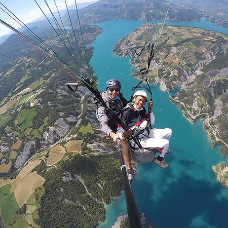 Equipage biplace parapente survolant en altitude le lac de Serre-Ponçon