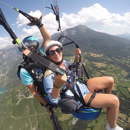 portrait de deux personnes en vol parapente biplace dans les Hautes Alpes
