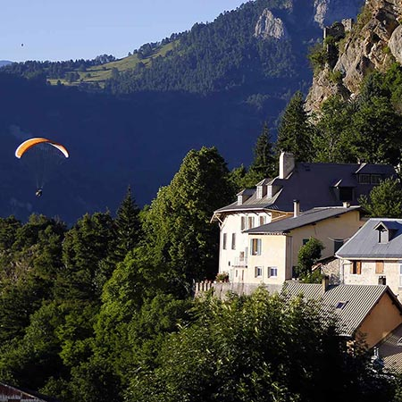 Parapente en survol devant maison de Saint Vincent les Forts.