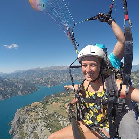 Jeune fille en vol parapente biplace au-dessus du lac de serre-ponçon