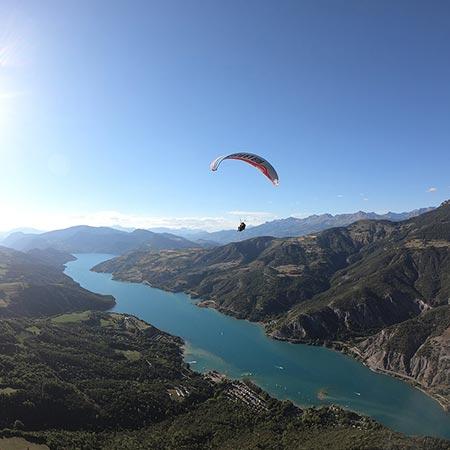 Vue d'un parapente en vol au dessus du lac de Serre-Ponçon.